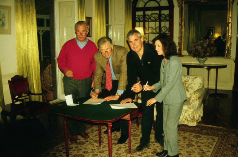 Stephen, second from left, signing the agreement to buy off the estuary nets in 2000