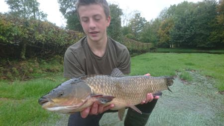 Thomas Macdonald-Ames with a 10lb grass carp he rescued from an orchard near Hay-on-Wye